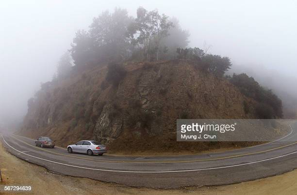 Cars negotiate a foggy Mulholland Drive in Studio City on Tuesday morning Overnight rain brought overcast skies and cooler temperatures to the Valley...