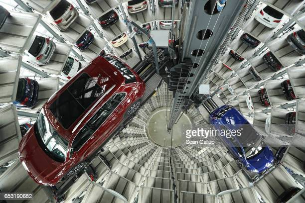 Cars of German automaker Volkswagen AG stand in one of the company's twin towers at its Autostadt customer center during the company's annual press...