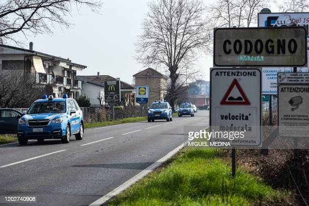 Cars of Italian National Police officers patrol on February 23 2020 at the entrance of the small Italian town of Codogno under the shadow of a new...