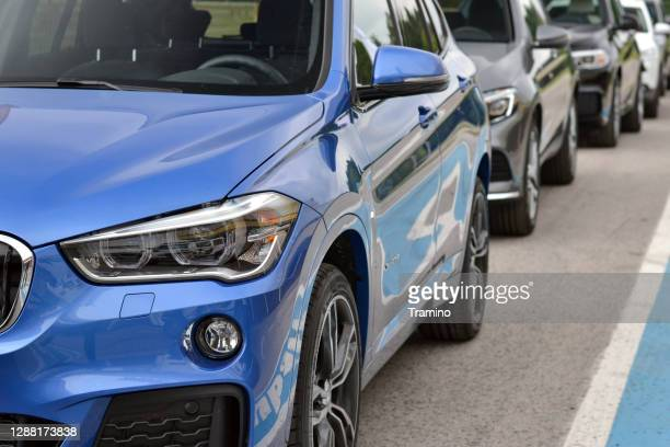 cars on a public parking on a street - bmw stock pictures, royalty-free photos & images