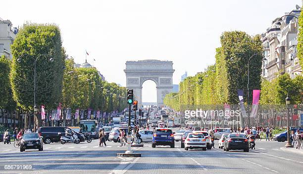 Cars On City Street By Arc De Triomphe Against Clear Sky