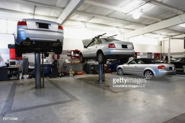 cars on hydraulic lifts at auto repair shop - auto repair shop stock pictures, royalty-free photos & images