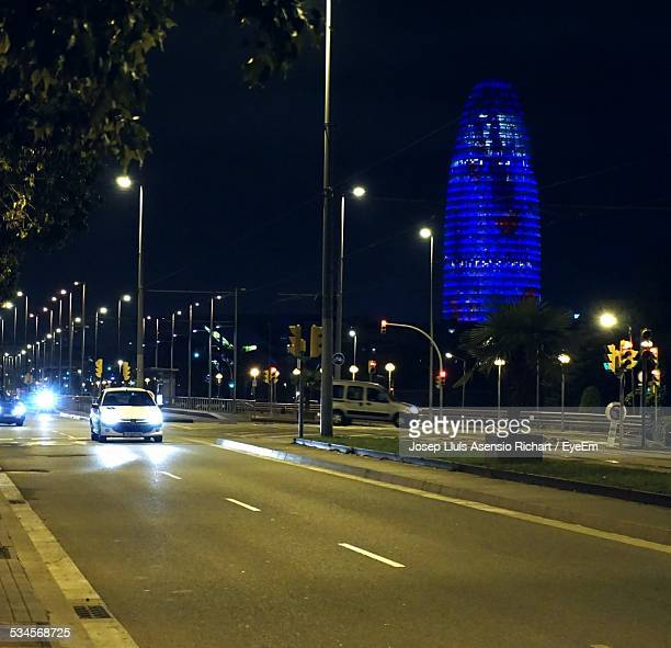 Cars On Illuminated City Street And Torre Agbar At Night