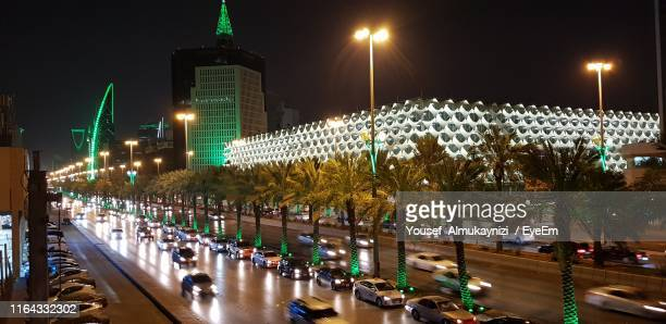 cars on illuminated street at night - riyadh stock pictures, royalty-free photos & images