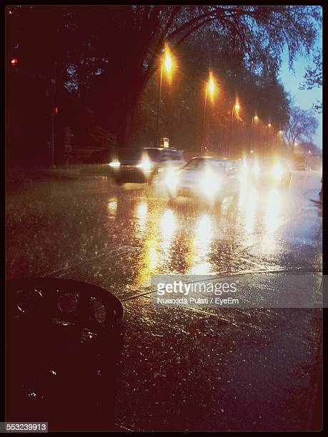 cars on illuminated street during rainy season - state college - fotografias e filmes do acervo