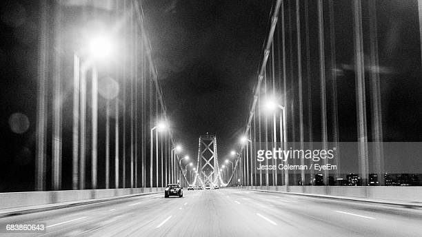 Cars On Illuminated Suspension Bridge At Night