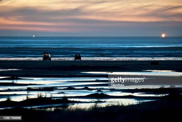 cars on oregon beach at dusk - fading stock pictures, royalty-free photos & images