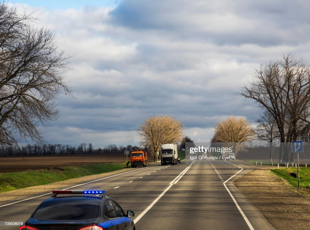 Cars On Road Against Cloudy Sky : Stock Photo