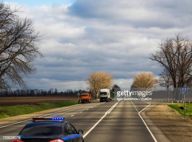 cars on road against cloudy sky - igor golovniov stock pictures, royalty-free photos & images