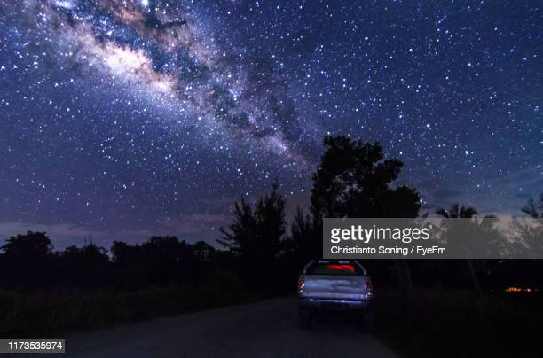 cars on road against sky at night - astronomy stock pictures, royalty-free photos & images