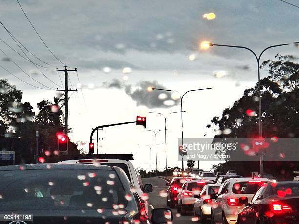 cars on road against sky at sunset during rainy season - red light stock pictures, royalty-free photos & images