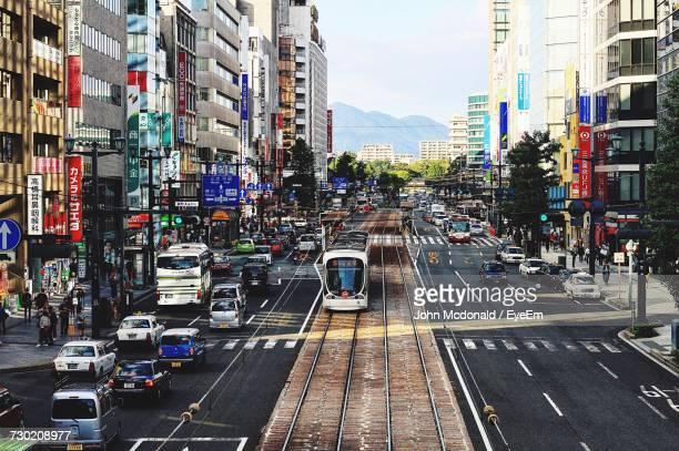 cars on road against sky in city - fukuoka city stock pictures, royalty-free photos & images
