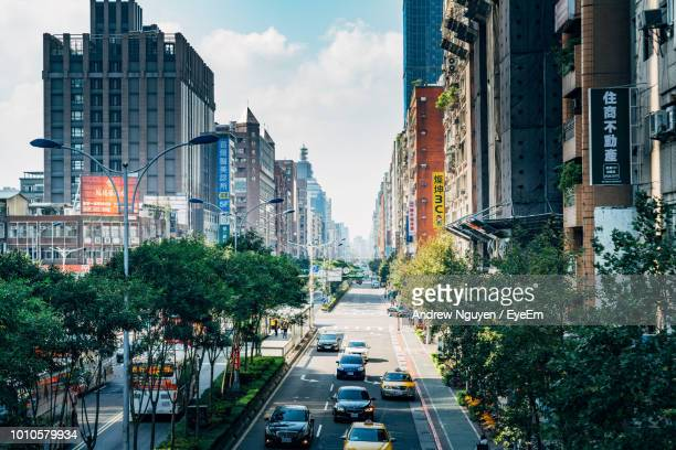 cars on road amidst buildings in city - taipei stock pictures, royalty-free photos & images
