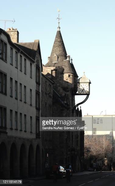 cars on road by buildings against sky in city - city gate stock pictures, royalty-free photos & images