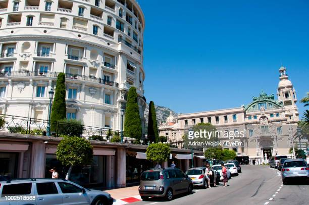 cars on road by buildings in city against clear sky - montecarlo foto e immagini stock