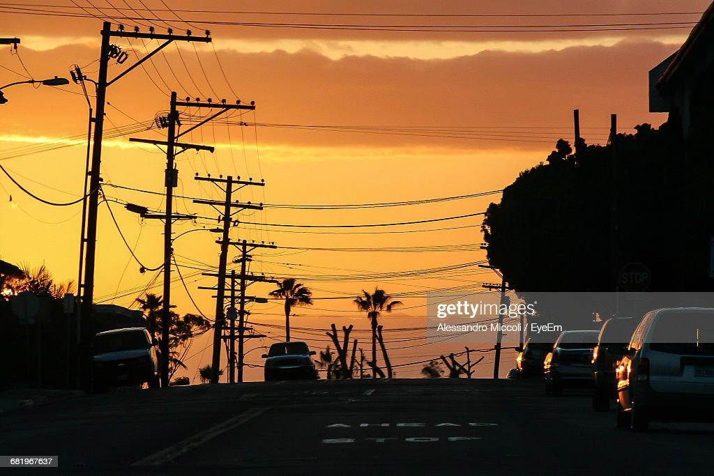Cars On Road By Electricity Pylons Against Orange Sky : Stock Photo