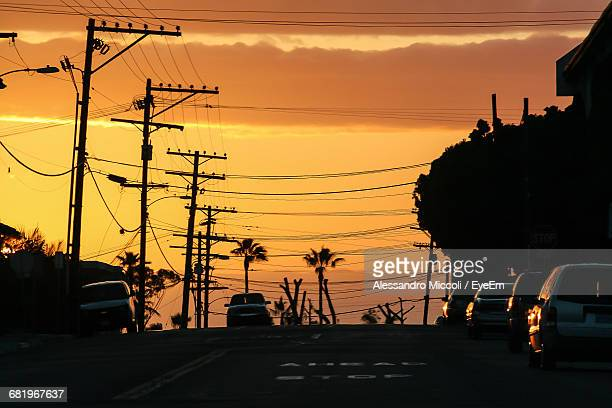 cars on road by electricity pylons against orange sky - alessandro miccoli stock photos and pictures