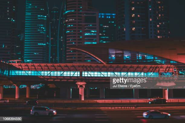 Cars On Road By Illuminated Buildings In City At Night