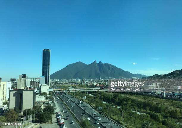 cars on road by mountain against blue sky - nuevo leon state stock pictures, royalty-free photos & images