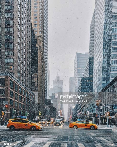 cars on road by towers in city during snowfall - midtown manhattan stock pictures, royalty-free photos & images
