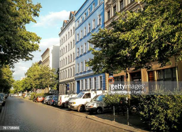cars on road by trees against sky in city - kreuzberg stock photos and pictures