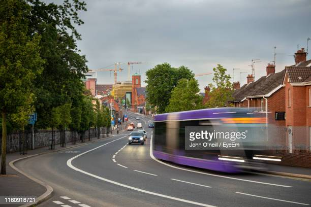 cars on road in city against sky - falls road stock pictures, royalty-free photos & images