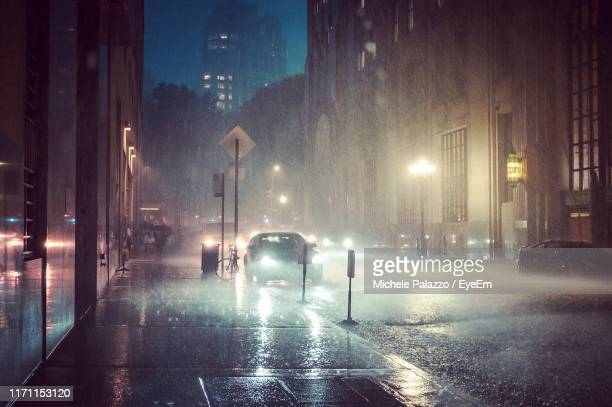 cars on road in city at night during rainy season - torrential rain stock pictures, royalty-free photos & images