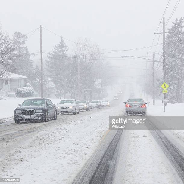 Cars on Road Moving Slowly in Winter Snowstorm