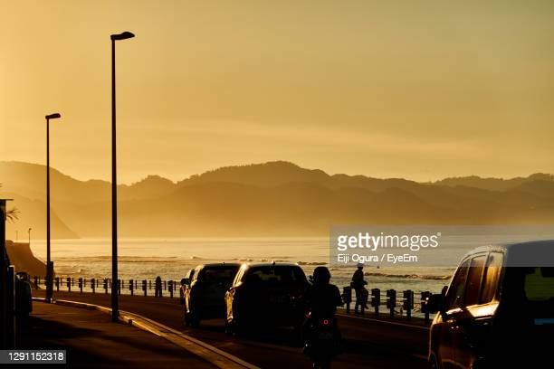 cars on street against sky during sunrise - kanagawa prefecture stock pictures, royalty-free photos & images
