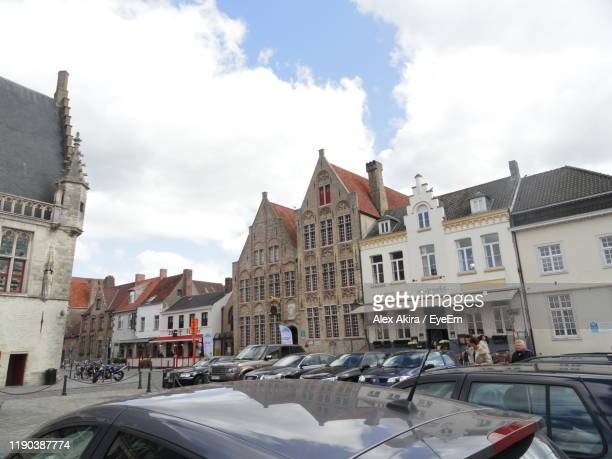 cars on street amidst buildings in town against sky - damme stock pictures, royalty-free photos & images