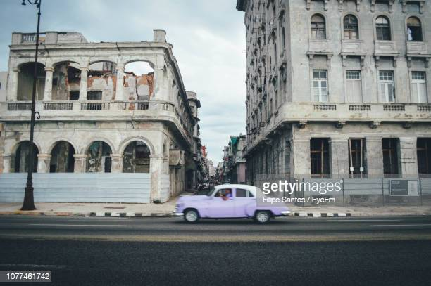 cars on street by buildings against sky in city - antilles stock pictures, royalty-free photos & images