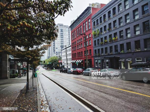 cars on street by buildings in city - vancouver canada stock pictures, royalty-free photos & images