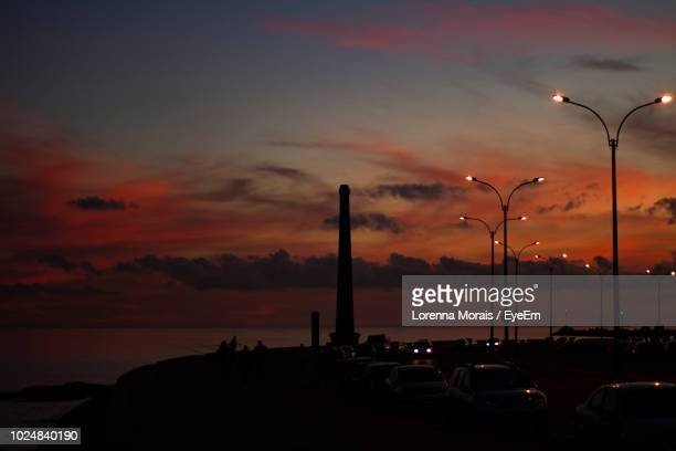 cars on street by sea against sky during sunset - lorenna morais - fotografias e filmes do acervo