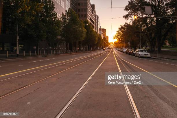 Cars On Street In City Against Sky At Sunset