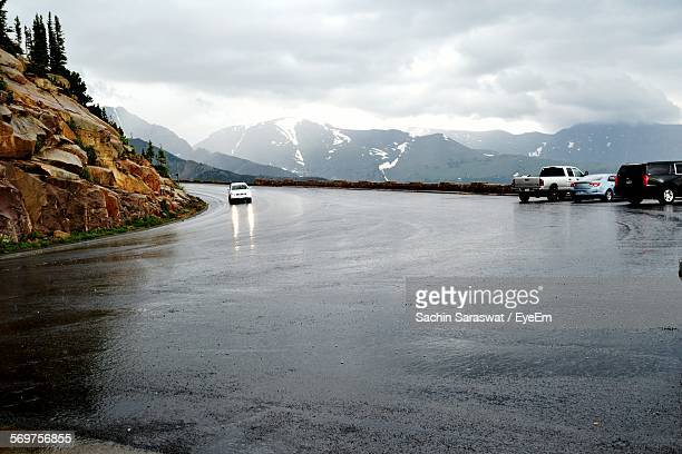 cars on wet road against mountains and cloudy sky - bagnato foto e immagini stock
