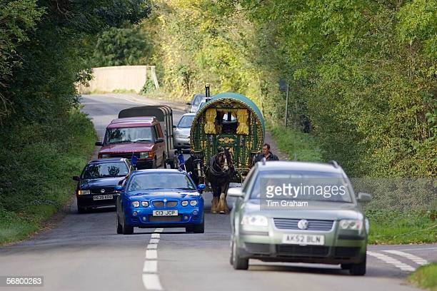Cars overtake shire horsedrawn gypsy caravan on country lanes StowOnTheWold Gloucestershire United Kingdom