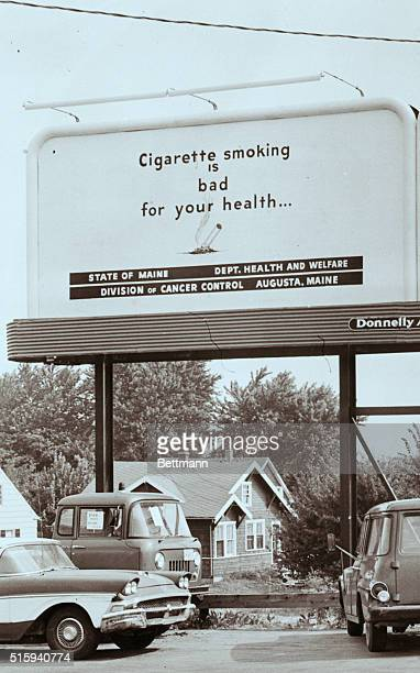 Cars park beneath a billboard stating 'Cigarette smoking is bad for your health' The billboard is one of thirty sponsored by the Division of Cancer...