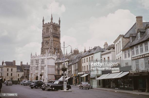 Cars parked and driving along Market Place with the parish Church of St John the Baptist in the background, in Cirencester, Gloucestershire, England...