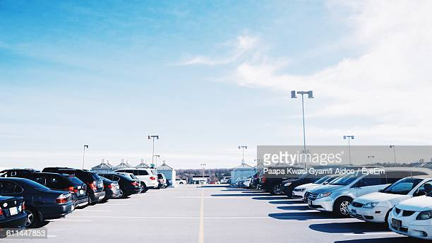 cars parked at parking lot against sky - car park stock pictures, royalty-free photos & images