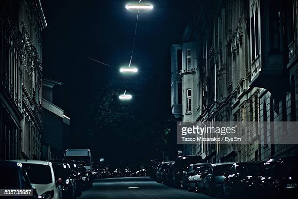 cars parked by buildings at city street during night - 固定された ストックフォトと画像
