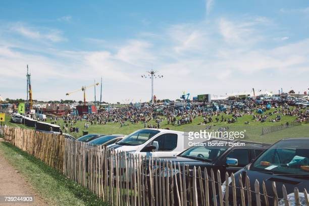 cars parked by fence at epsom downs racecourse against sky - bortes stock-fotos und bilder