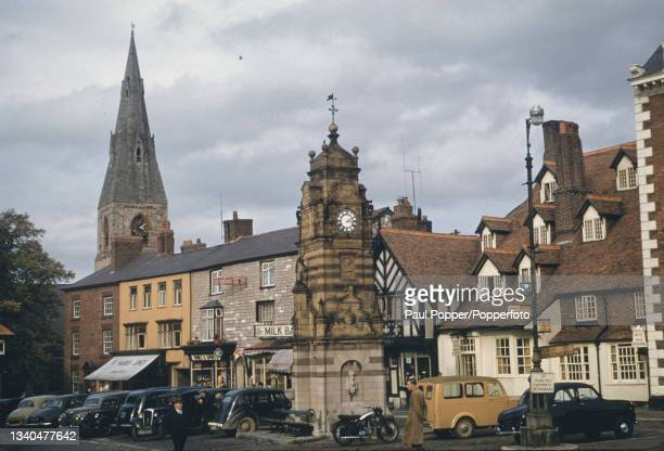 Cars parked by the clocktower on St Peter's Square in the market town of Ruthin in Denbighshire, Wales circa 1960. The spire of St Peter's Church is...