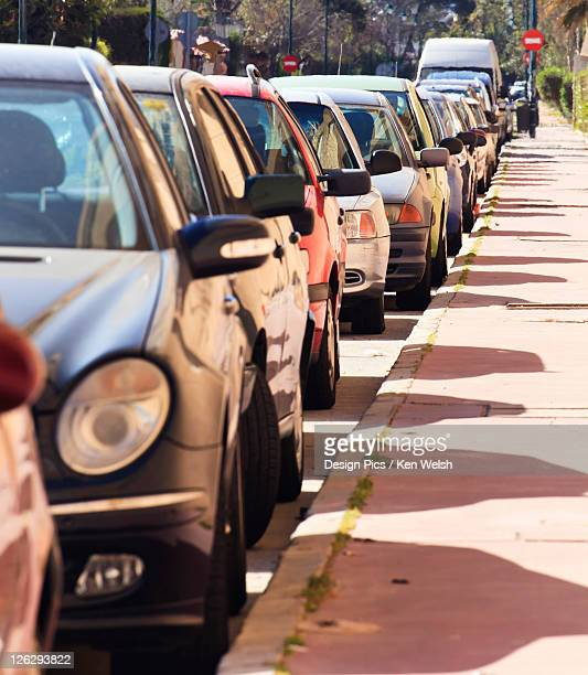 cars parked in line on street - curb stock pictures, royalty-free photos & images