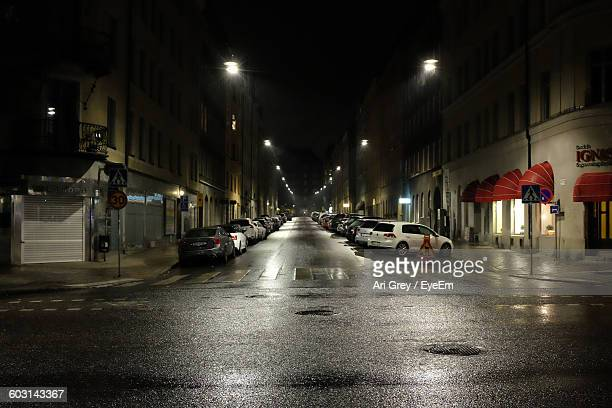 cars parked in row on roadside at night - fermo foto e immagini stock