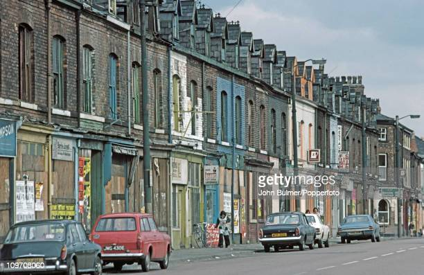 Cars parked on a street of boarded up shops Manchester England in 1976