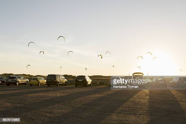 Cars parked on beach against parachutes in sky during sunset