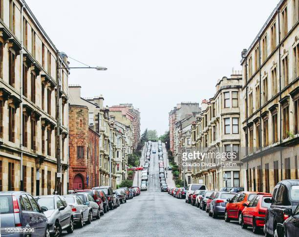 cars parked on road amidst buildings against clear sky - glasgow scotland stock pictures, royalty-free photos & images