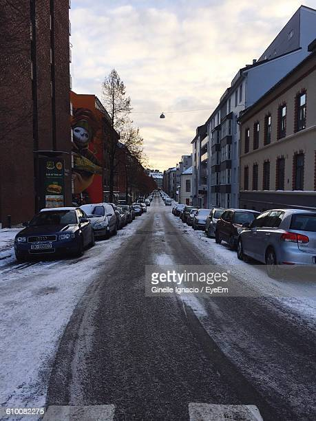 Cars Parked On Roadside Amidst Buildings In City During Winter