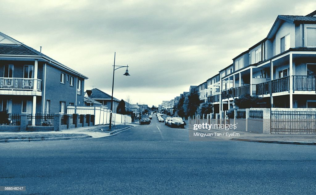Cars Parked On Roadside By Residential Houses Against Sky : Stock Photo