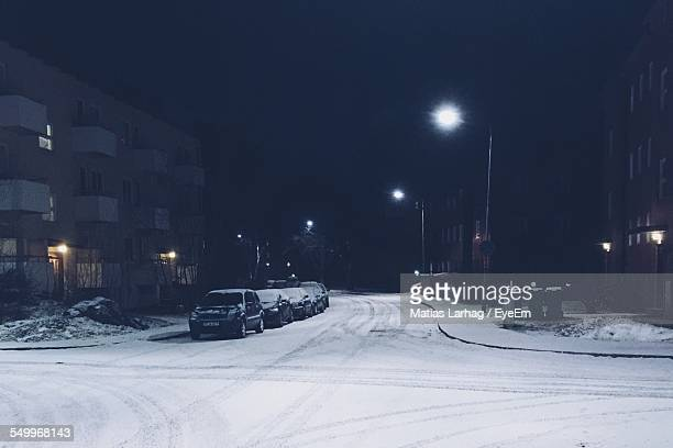 Cars Parked On Snow Covered Road By Buildings
